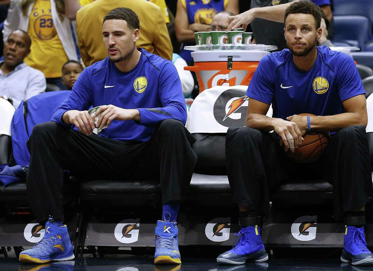 Stephen Curry #30 of the Golden State Warriors (R) and Klay Thompson #11 sit on the bench before a game against the New Orleans Pelicans at the Smoothie King Center on December 4, 2017 in New Orleans, Louisiana.