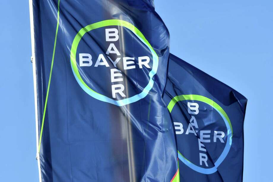 The logo of German chemicals giant Bayer is seen on flags during the company's annual results press conference on February 28, 2018 in Leverkusen.  German chemicals and pharmaceuticals giant Bayer said on February 28, 2018 that its profits soared 2017 and it is confident the planned mega-merger with US seeds and pesticides maker Monsanto will go ahead this year. Net profit at the Leverkusen-based maker of Aspirin jumped 62 percent to 7.3 billion euros ($8.9 billion) last year.  / AFP PHOTO / Patrik STOLLARZPATRIK STOLLARZ/AFP/Getty Images Photo: PATRIK STOLLARZ / AFP or licensors