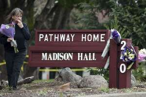 A woman reacts while placing flowers at a sign where a hostage situation with an active shooter came to a tragic end the night before at the Veterans Home of California in Yountville, Calif. on Saturday, March 10, 2018. Four people were killed, including the shooter.