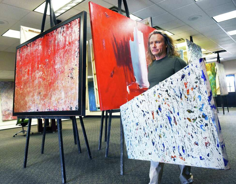 Artist Michael Nighswonger sets up 45 of his contemporary abstract acrylic on canvas works for a 10-day pop-up exhibit inside the old bank Thursday March 15, 2018 in Delmar, NY. (John Carl D'Annibale/Times Union)