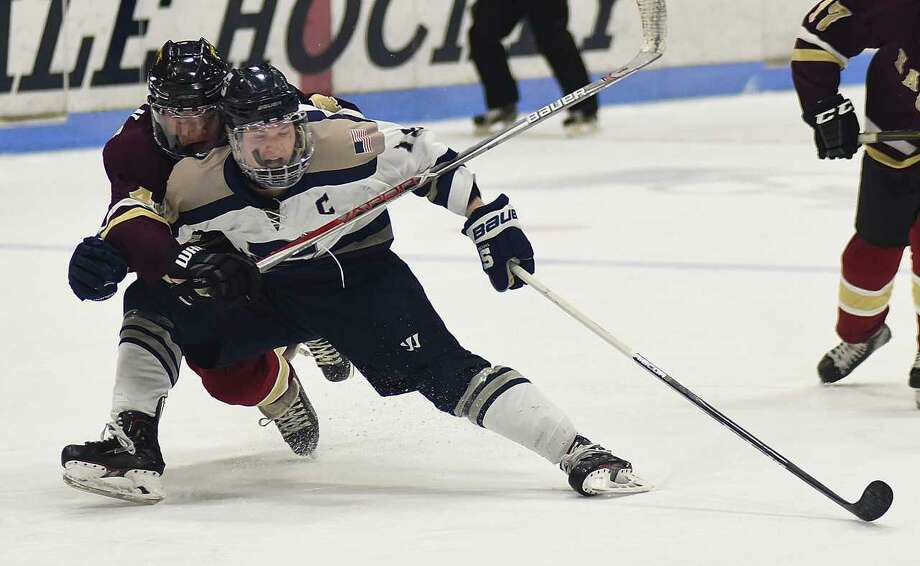 Staples' Sam New, front, is dragged down from behind on a breakaway attempt by an Eastern Connecticut player during the first period of Thursday's Division III semifinals at Ingalls Rink in New Haven. No penalty was called on the play. Photo: John Nash / Hearst Connecticut Media