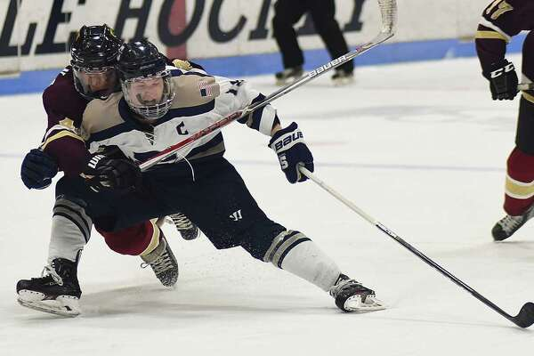 Staples' Sam New, front, is dragged down from behind on a breakaway attempt by an Eastern Connecticut player during the first period of Thursday's Division III semifinals at Ingalls Rink in New Haven. No penalty was called on the play.