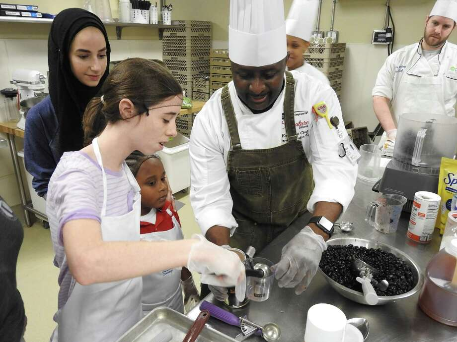 Students Scottie Denton and Sir Channing Veasley work with chef Donald Mutin, as Next Step Academy teacher Eman Mutasheb, left, and chefs Keesha Oldham and Adam Perkey look on.