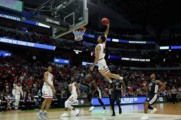 Texas Tech's Zach Smith, top, soars to the basket past a pair of Stephen F. Austin defenders for a dunk Thursday night.
