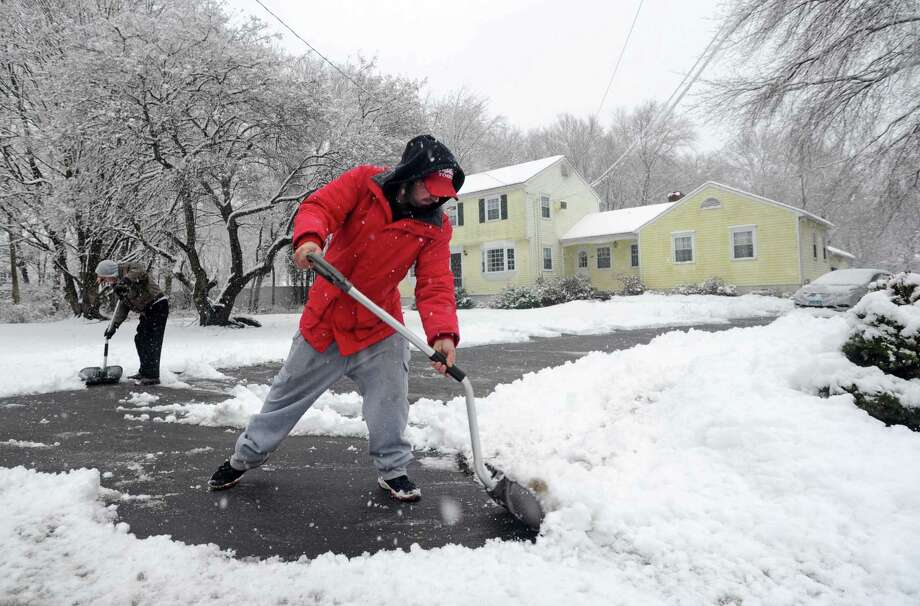 Sal Uscilla, right, helps his dad, Chuck Uscilla, clear the driveway on Long Lots Road in Westport on Tuesday. Photo: Cathy Zuraw / Hearst Connecticut Media / Connecticut Post