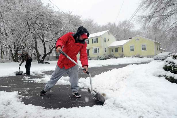 Sal Uscilla, right, helps his dad, Chuck Uscilla, clear the driveway on Long Lots Road in Westport on Tuesday.