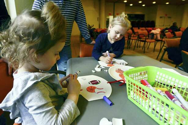 From left, Maeve Kennedy, 3 of New Canaan and her cousin Grace Kennedy, 4, of Stamford decorate basketball hoops during March Madness Storycraft hour at the Ferguson Library on Friday, March 10, 2018 in Stamford, Connecticut. Children and adults listen to stories and created colorful decorated basketball hoops that the could use to play fun indoor games at home. Several dozen families participated in the event at the library, which hosts different activities throughout the month. For a listing of events, please visit www.fergusonlibrary.org.