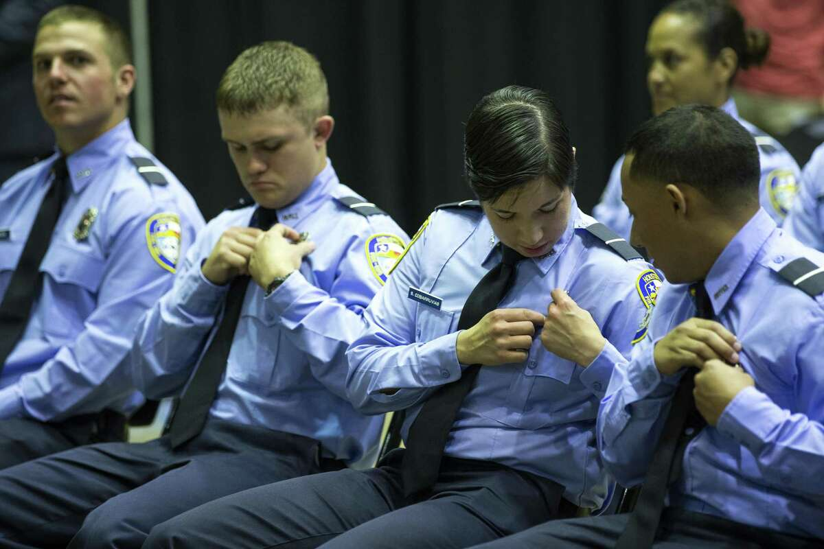 New firefighters Blake Balcerek, Sarah Cobarruvis and Henry Cuellar adjust their new badges during the graduation ceremony for the Houston Fire Department Cadet Class 2018-A at the Val Jahnke Training Facility on Thursday, March 8, 2018, in Houston. ( Brett Coomer / Houston Chronicle )