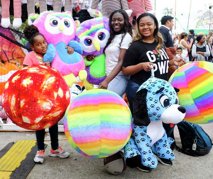"""Mariah Mitchell, 11, from left, poses with her cousins Jurnee, 16, and Tanrra Young, 15, with their big winnings. The Humble residents get a lot of basketball practice in at home and were able to translate their skills this year on the midway. """"Usually we just win small items, but this year, we just keep winning big!"""" said Tanarra.  Lucky attendees show off their winnings from the midway at Houston Livestock Show and Rodeo at NRG Stadium on  on Thursday, March 15, 2018, in Houston."""