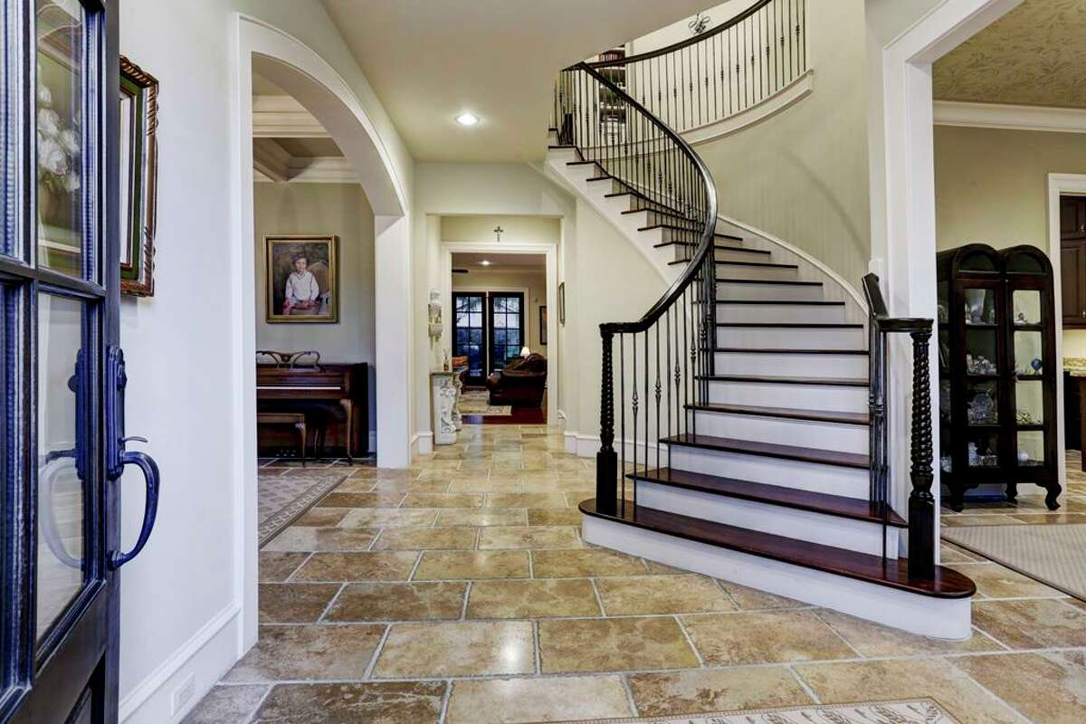 Before: Guests are greeted by travertine floors and an ordinary staircase.