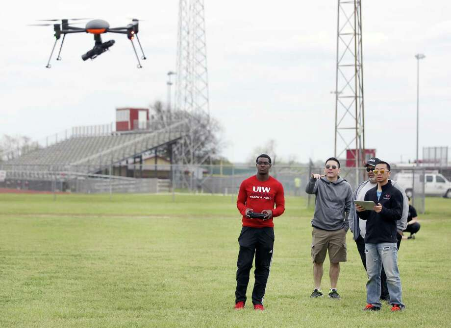 UIW Autonomous Vehicle Systems Lab Unmanned Air Systems pilot Jordan Epps, left, flies a quadcopter Thursday, March 16, 2018 at Southside High School during a maiden outdoor flight while Michael Frye, associate prof of engineering at UIW, second from left, watches. Also seen are Andrew Chavez, wearing hat, and Jack Han. Photo: William Luther, Staff / San Antonio Express-News / © 2018 San Antonio Express-News