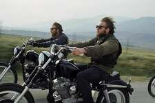 Hell's Angels riding motorcycles on road.