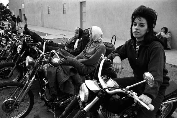 Several 'Old Ladies,' the girlfriends of Hells Angels motorcycle club members, sit on parked bikes during a rest stop on their run from San Bernardino to Bakersfield, California, 1965. (Photo by Bill Ray/The LIFE Picture Collection/Getty Images)