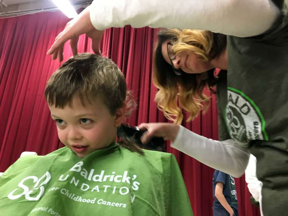 Rory Resig, a kindergarten student at Stratfield School, gets shaved by Gigi Molony at Stratfield School's 10th annual St. Baldrick's event in Fairfield, Conn. on Wednesday, March 14, 2018.  Over the years, the school has raised more than $550,000 000 for pediatric cancer research. This year more than 130 participants raised over $62,000. Photo: Joan Filan McBennet / For Hearst Connecticut Media / Connecticut Post Freelance