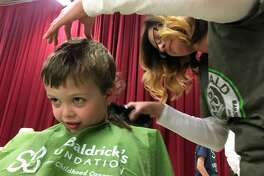 Rory Resig, a kindergarten student at Stratfield School, gets shaved by Gigi Molony at Stratfield School's 10th annual St. Baldrick's event in Fairfield, Conn. on Wednesday, March 14, 2018.  Over the years, the school has raised more than $550,000 000 for pediatric cancer research. This year more than 130 participants raised over $62,000.