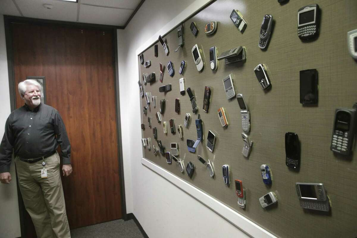 Dave Wolter, assistant vice president of radio technology and strategy at AT&T, shows off a display board of old phones at AT&T's Austin 5G lab. The 5G technology, shorthand for the fifth generation of wireless networks, is the next step in building a critical infrastructure to power the future