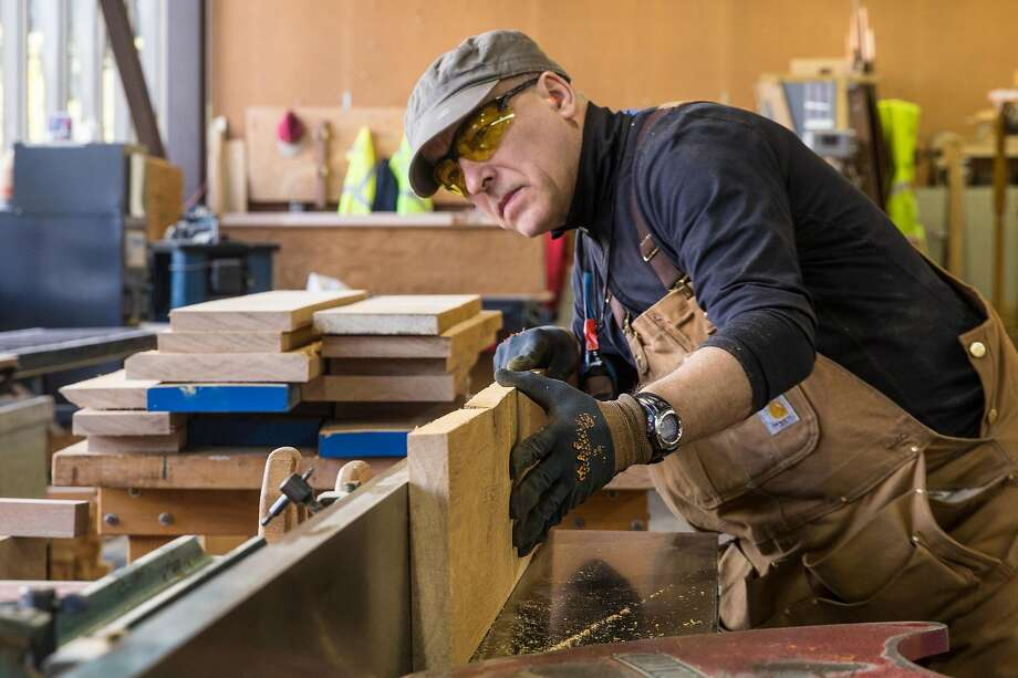 Master craftsman Luis Ferreira shapes a piece of wood for a cable car's window frame. Photo: Jessica Christian, The Chronicle