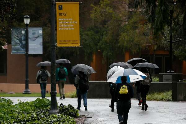 Students walk through the UC Berkeley campus on Friday, March 16, 2018. A series of storms continue to douse the Bay Area.