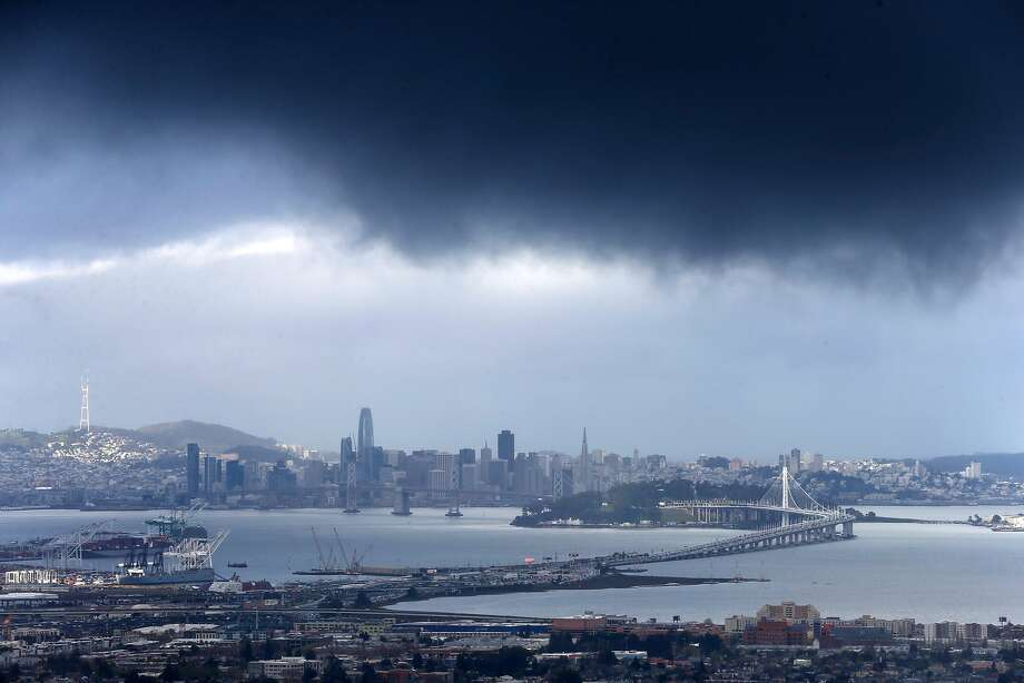 Dark clouds hang above the East Bay in Oakland, while San Francisco has a chance to dry out. A series of storms continues to douse the Bay Area. Photo: Paul Chinn, The Chronicle