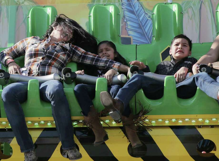Abigail Zuniga holds onto her children Evelyn and Lalo Cruz as they enjoy a ride at the Midway of the Houston Livestock Show and Rodeo on Tuesday, March 13, 2018, in Houston. Photo: Elizabeth Conley, Houston Chronicle / © 2018 Houston Chronicle