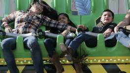 Abigail Zuniga holds onto her children Evelyn and Lalo Cruz as they enjoy a ride at the Midway of the Houston Livestock Show and Rodeo on Tuesday, March 13, 2018, in Houston.