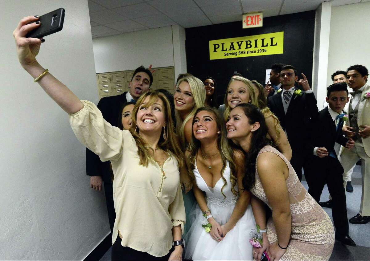 """Toni Ann Canora, a parent and Event Chair, snaps a selfie with some of the seniors who modeled various prom fashions during Stamford High School's Junior/Senior """"A Starry Knight"""" fashion show on Thursday, March 15, 2018 in Stamford, Connecticut. The event, in its 30th year, raised over $7,000 dollars for the SHS 2018 after-prom party, which will be held in the gym at Davenport Elementary School."""