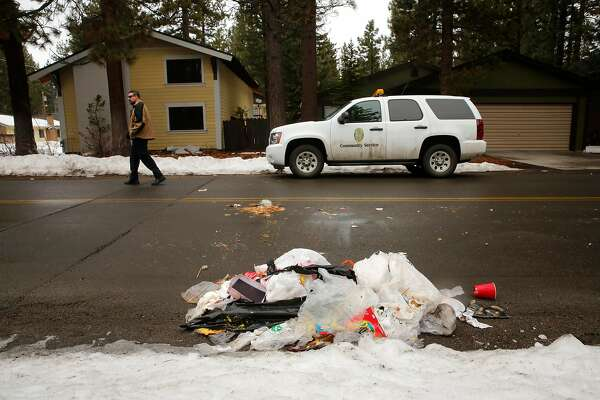 """South Lake Tahoe Police, community service officer and vacation house rental specialist, Louis Klingelhoffer walks through the Al Tahoe neighborhood where a pile of trash, which may be the work of a bear, lies in the roadway in South Lake Tahoe, Calif., on Sun. March 11, 2018. One of the ordinances requires all trash to be deposited in a """"Bear box"""" in front of the home. The City of South Lake Tahoe has a strict Vacation Home Rental Ordinance (VHR) with fines of $1,000 for violations."""