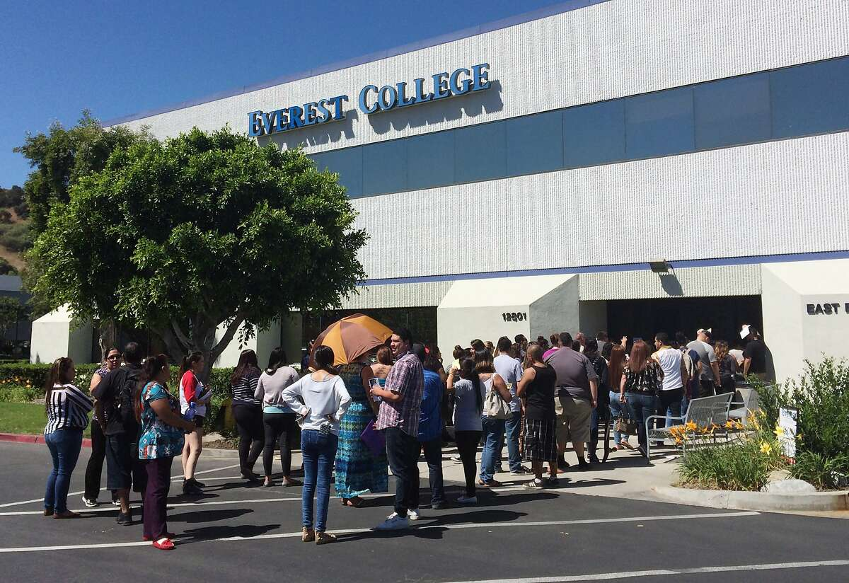 FILE - In this April 28, 2015 file photo, students wait outside Everest College in Industry, Calif., hoping to get their transcriptions and information on loan forgiveness and transferring credits to other schools. Almost 12,000 students are asking the federal government to discharge their college loan debt, asserting that their school either closed or lied to them about job prospects, according to government data released Thursday. The figure represents an unprecedented spike in what's called a