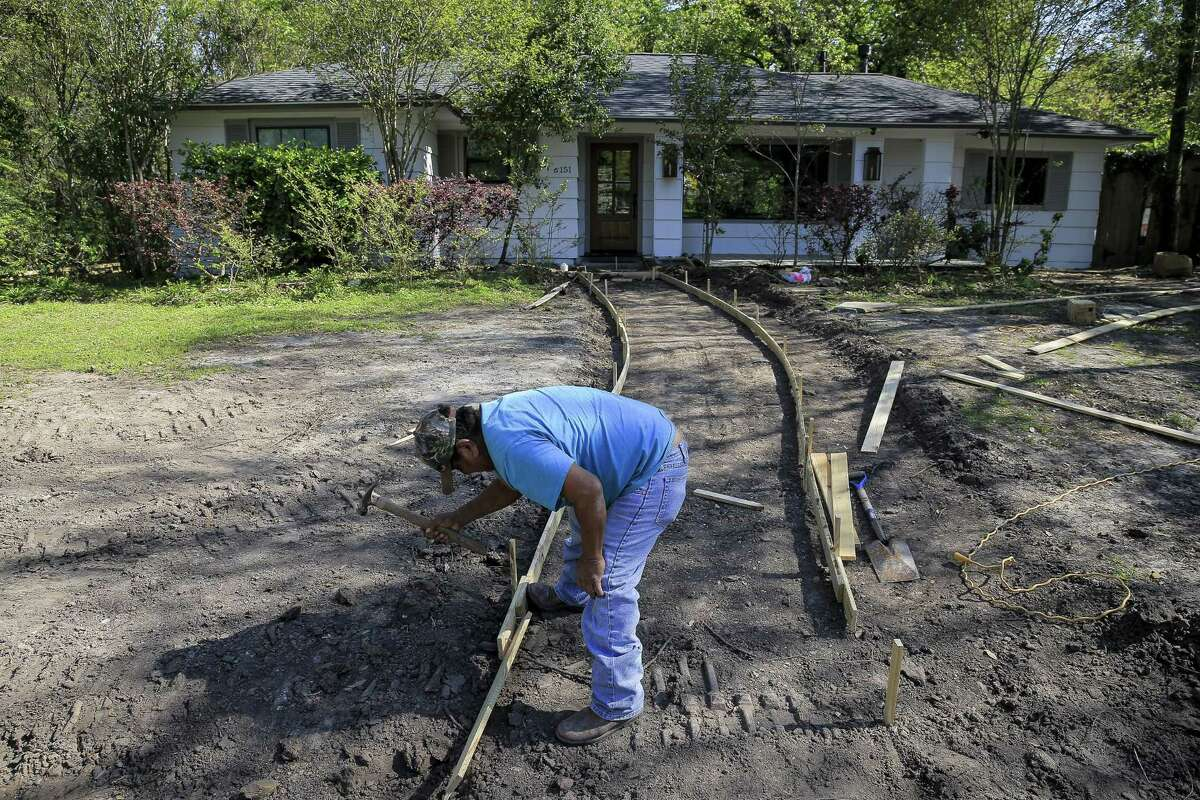Concrete worker Ramirez Ebrardo frames out a walkway in front of a home in the Timbergrove neighborhood Tuesday, March 13, 2018 in Houston. The proposed North Canal project, a project that would cut a 1,300-foot channel north of the convergence of White Oak and Buffalo Bayou and remove and rebuild bridges over White Oak Bayou, could remove parts of the Timbergrove neighborhood from the 100-year floodplain. (Michael Ciaglo / Houston Chronicle)