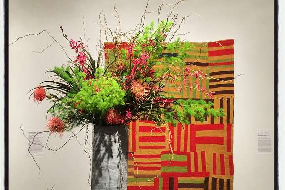 """A Bouquets to Art floral tribute by Kirk Wilder and Acme Floral Co. pays homage to """"Roman Stripes"""" by artist Willie """"Ma Willie"""" Abrams at the de Young Museum. March 12, 2018."""
