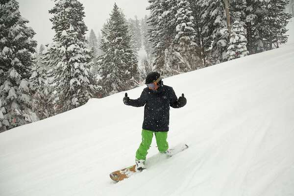 In this photo provided by Northstar California, a snowboarder slides through fresh snow at the Northstar California Resort, Friday, March 16, 2018, in Truckee, Calif. A late-winter storm moving through California is piling up snow in the Sierra Nevada, making travel hazardous and raising avalanche danger. The National Weather Service says the Heavenly and Northstar ski resorts near Lake Tahoe reported Friday morning they each received more than 2 feet of snow in 24 hours. (Colin Lygren/Northstar California via AP)