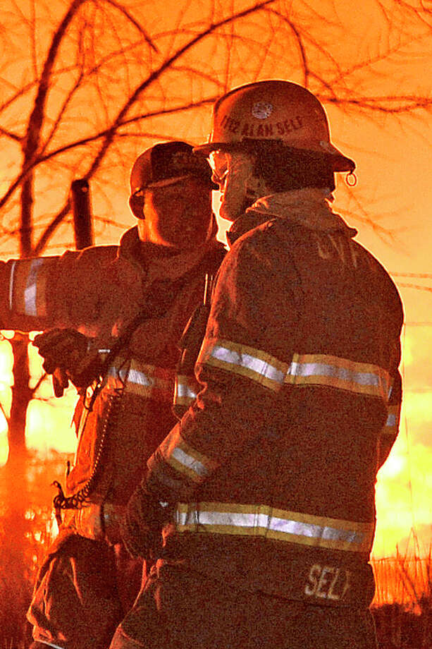 Members of the Midland Fire Department and surrounding volunteer departments work a massive fire at Trinity Pallets, Inc. on S. Highway 349 that started late on the night of Feb. 3, 2018, and continued into the early morning hours of Feb. 4. Pictured in right foreground, Alan Self, of the Greenwood Volunteer Fire Department, was later arrested and charged with arson for multiple fires including the one pictured at Trinity Pallets, Inc. James Durbin/Reporter-Telegram Photo: James Durbin