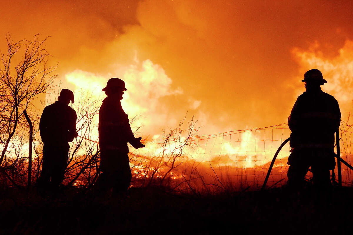 Members of the Midland Fire Department and surrounding volunteer departments work a massive fire at Trinity Pallets, Inc. on S. Highway 349 that started late on the night of Feb. 3, 2018, and continued into the early morning hours of Feb. 4. Pictured in center, Alan Self, of the Greenwood Volunteer Fire Department, was later arrested and charged with arson for multiple fires including the one pictured at Trinity Pallets, Inc. James Durbin/Reporter-Telegram