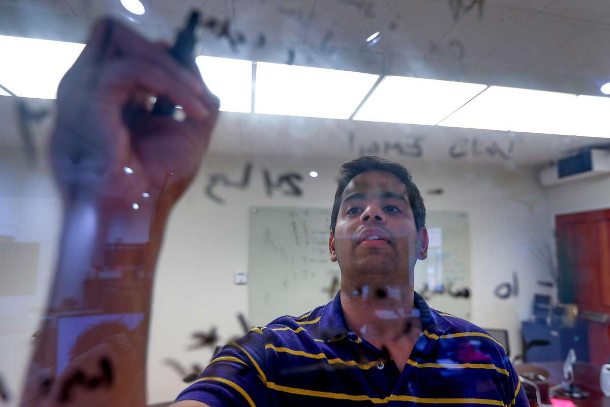 Ayush Chordia, director of engineering, uses a marker pen to write a technical formula on glass in a meeting room at the at the Voicera offices in Menlo Park, Calif., on Thursday, Mar. 15, 2018. Voicera is the creator of Eva, a voice-activated A.I. platform that improves in-meeting and post-meeting experiences using Eva to listen in, take notes & identify key actions.