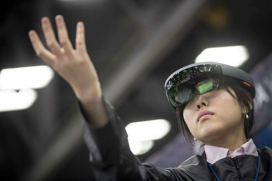 An attendee wears a Microsoft Corp. HoloLens headset at the South By Southwest (SXSW) conference in Austin, Texas, U.S., on Tuesday, March 13, 2018. Amid the raucous parties and speed networking at the annual festival that draws people from technology, film, and music to Austin, Texas, there will be some soul searching about gender discrimination, sexual harassment and how to fix the broken workplace culture. Photographer: David Paul Morris/Bloomberg Photo: David Paul Morris / Bloomberg / © 2018 Bloomberg Finance LP