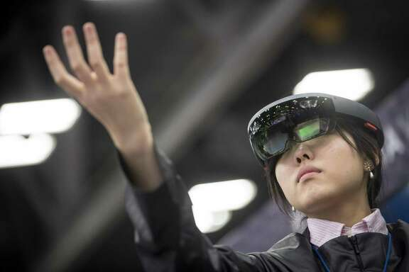 An attendee wears a Microsoft Corp. HoloLens headset at the South By Southwest (SXSW) conference in Austin, Texas, U.S., on Tuesday, March 13, 2018. Amid the raucous parties and speed networking at the annual festival that draws people from technology, film, and music to Austin, Texas, there will be some soul searching about gender discrimination, sexual harassment and how to fix the broken workplace culture. Photographer: David Paul Morris/Bloomberg