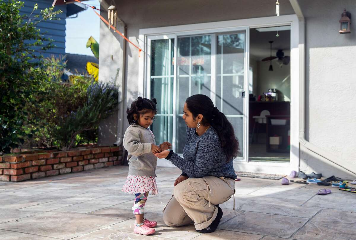 Renuka Sivarajan solves a problem with Sanjana, 3, Wednesday, Jan. 17, 2018 in the backyard of her home and day care center in Fremont, Calif.