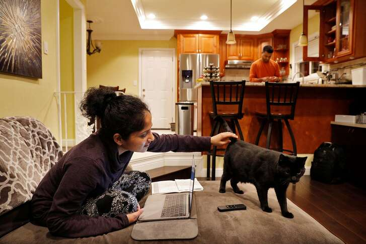 Preethi Rao, right, plays with her cat Lulu as her husband, Sudarshan Bhat, right, peels a pomegranate at their home in San Jose, Calif., on Thursday, January 18, 2018. Bhat has been in the U.S. for about 11 years on an H-1B visa and, at this rate, he won't get his green card for another 50+ years. He is one of thousands of Indians living in the U.S. who are stuck in Green Card backlog so bad that they are more likely to die before they get permanent residency into the U.S. Without a green card, people like Sudi live in constant uncertainty if they will get their H-1B visa renewed. And after investing in a house, car and life here in the U.S. -- leaving the country isn't much of an option.