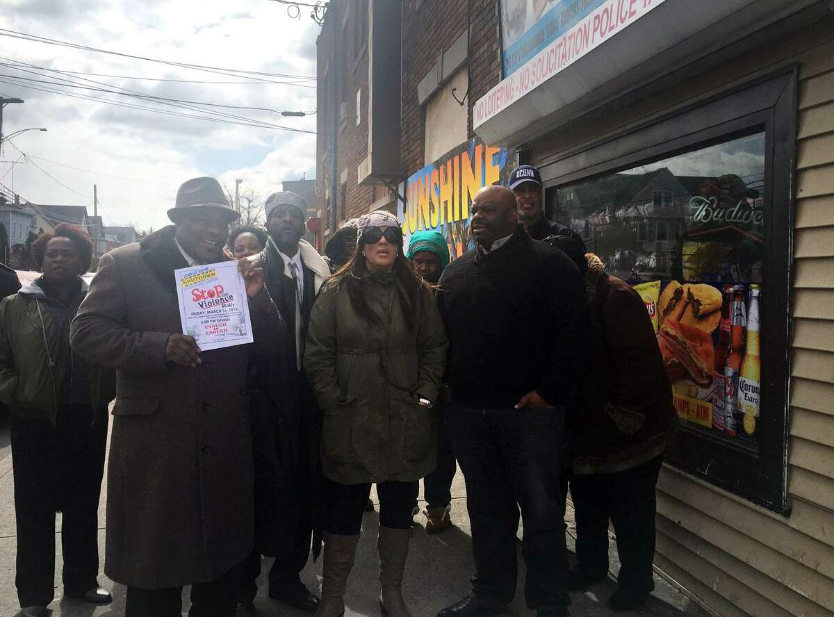 City council members Ernie Newton and Eneida Martinez, center, and other community leaders gathered outside of Sunshine Deli on Stratford Avenue on Friday to call for a change to the store's operating hours to help deter violence.