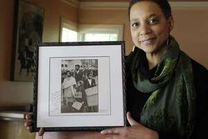 """Hasna Muhammad of Brewster, daughter of the late actors and activists Ruby Dee and Ossie Davis, holds of photo of herself with her parents and siblings taken in the early '60s on Thursday. The children are holding signs that read """"No War."""" Photo credit: Bruce Davidson at Magnum Photos."""