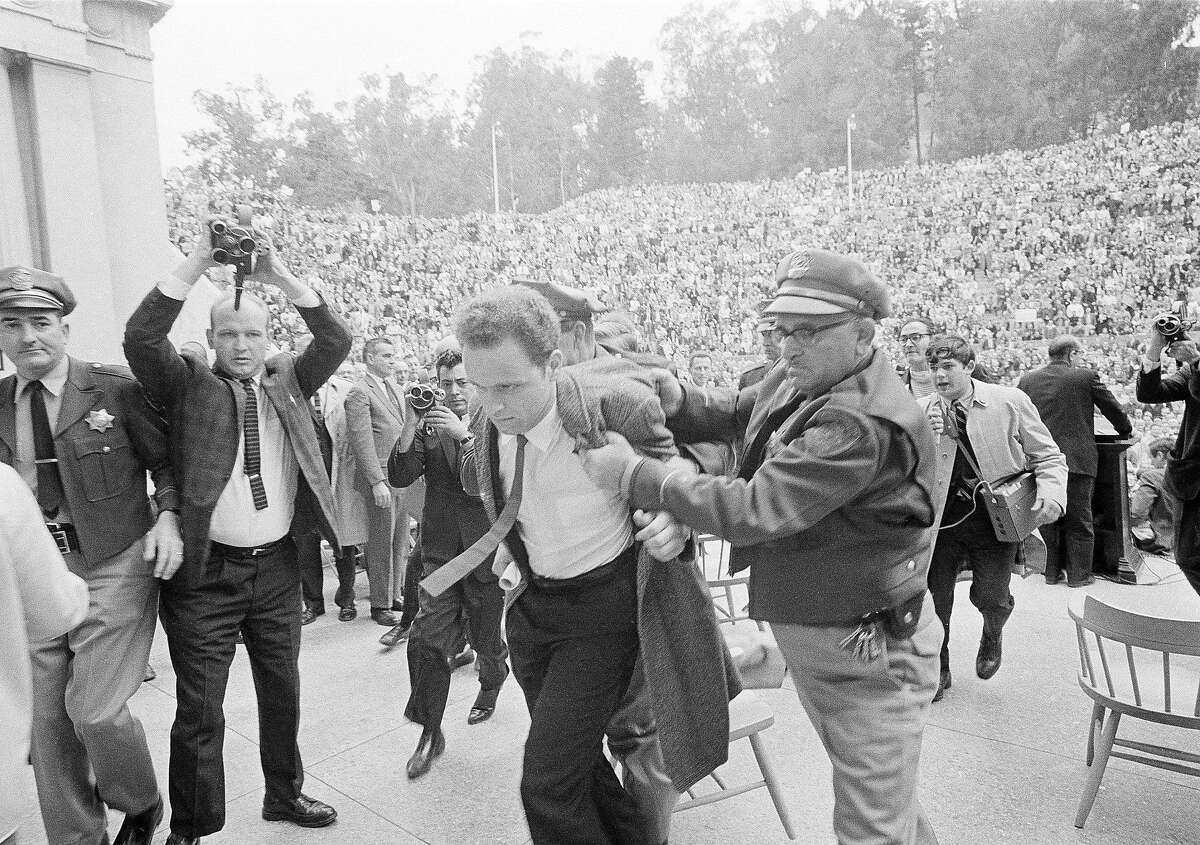 FILE - In this Dec. 7, 1964 file photo, Mario Savio, leader of the Berkeley Free Speech Movement, is restrained by police as he walks on to the platform at the University of California's Greek Theater in Berkeley, Calif. Savio attempted to speak directly following the appearance of University President Clark Kerr. He was later permitted to make two announcements to the assembled students. The fall of 2014 marks the 50th anniversary of the Free Speech Movement, a protest that only lasted for three months but set the stage for the turbulent 1960s. (AP Photo/Robert W. Klein, File)
