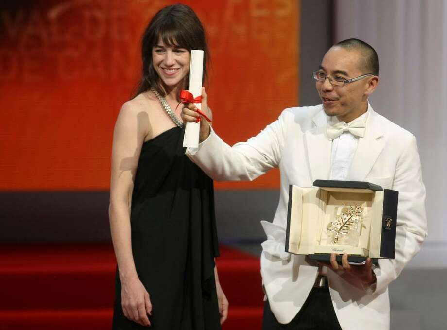 Director Apichatpong Weerasethakul, right, receives the Palme d'Or award from actress Charlotte Gainsbourg, left, during the awards ceremony at the 63rd international film festival, in Cannes, southern France, Sunday, May 23, 2010. (AP Photo/Lionel Cironneau) Photo: Lionel Cironneau