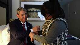 """Erika Prosper helps put on cufflinks bearing the Penn shield she surprised for her husband, Ron Nirenberg, as he looks on in admiration, in their hotel room Monday, March 12, 2018 in Philadelphia, Pa. The San Antonio Mayor presented the 2018 George Gerbner Lecture in Communication """"Be a Better Neighbor: The Education of a Mayor,"""" at the Annenberg School for Communication at the University of Pennsylvania as well as coming to visit his old collegiate stomping grounds with his family. Meeting his wife there, and his first time back with his son, Ron attributes his experience at Penn as part of shaping the person and political leader he has become. (Corey Perrine/For the San Antonio Express-News)"""