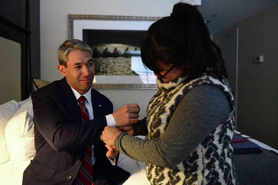 """Erika Prosper helps put on cufflinks bearing the Penn shield she surprised for her husband, Ron Nirenberg, as he looks on in admiration, in their hotel room Monday, March 12, 2018 in Philadelphia, Pa. The San Antonio Mayor presented the 2018 George Gerbner Lecture in Communication """"Be a Better Neighbor: The Education of a Mayor,"""" at the Annenberg School for Communication at the University of Pennsylvania as well as coming to visit his old collegiate stomping grounds with his family. Meeting his wife there, and his first time back with his son, Ron attributes his experience at Penn as part of shaping the person and political leader he has become. (Corey Perrine/For the San Antonio Express-News) Photo: Corey Perrine /San Antonio Express-News / 2018 Corey Perrine"""
