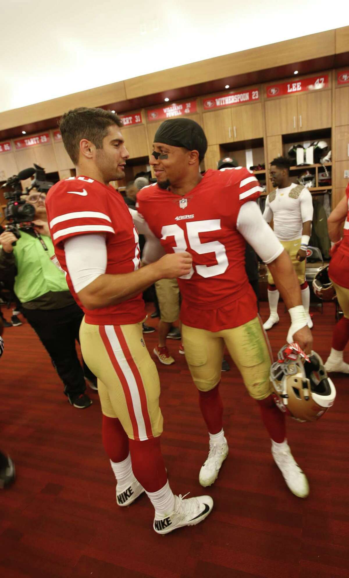 Jimmy Garoppolo #10 and Eric Reid #35 of the San Francisco 49ers celebrate in the locker room following the game against the Tennessee Titans at Levi's Stadium on December 17, 2017 in Santa Clara, California. The 49ers defeated the Titans 25-23.