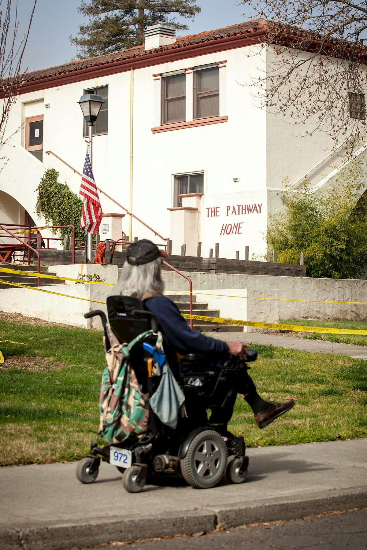 An unidentified resident of the Veteran Home of California rolls passed the front entrance of the Pathway Home where three employees of Pathway were killed by a former patient on Friday March 09 in Yountville, California, USA 11 Mar 2018.