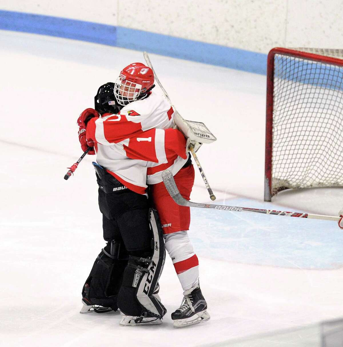 Andrew Frost, right, of Greenwich, hugs his goalie Ben Nash after teammate Matthew Davey scored the winning goal in overtime to defeat Xavier 3-2 during the CIAC Division I boys ice hockey semifinals on Wednesday.