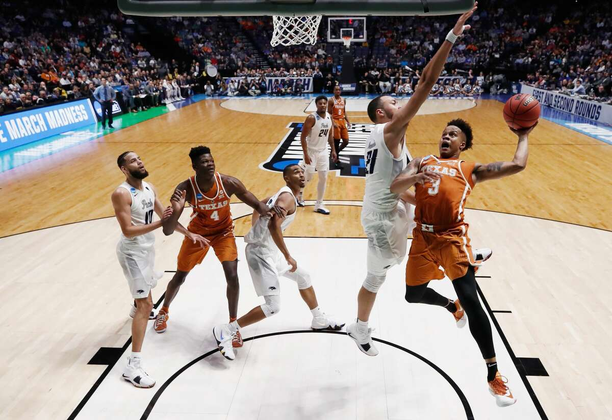 NASHVILLE, TN - MARCH 16: Jacob Young #3 of the Texas Longhorns goes up for a layup defended by Kendall Stephens #21 of the Nevada Wolf Pack during the game in the first round of the 2018 NCAA Men's Basketball Tournament at Bridgestone Arena on March 16, 2018 in Nashville, Tennessee. (Photo by Andy Lyons/Getty Images)