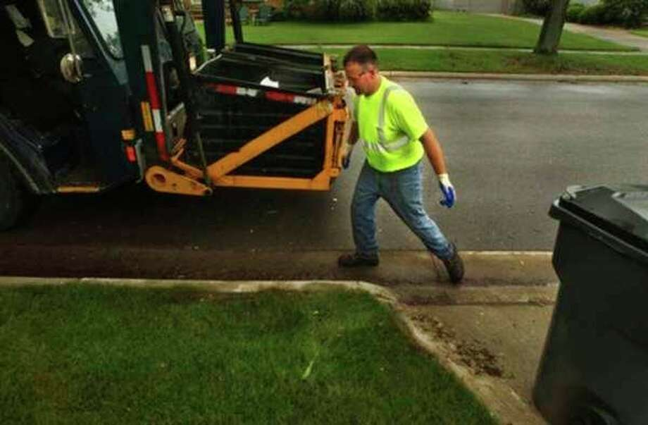 FILE: In this file photo, a City of Midland Public Works employee collects refuse from a residential area to deposit in a dual stream front load truck.