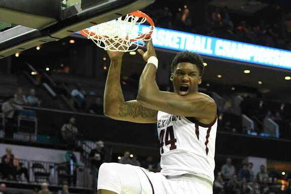 "Texas A&M's Robert Williams reacts after his ""nasty"" dunk against Providence during an NCAA Tournament first-round game at the Spectrum Center in Charlotte, N.C., on Friday."